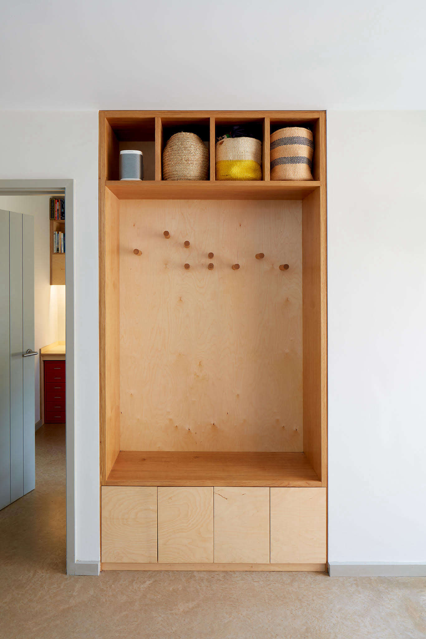 In the entry, a plywood built-in wardrobe features pegs (for hanging outerwear) arranged to replicate the profile of the house.