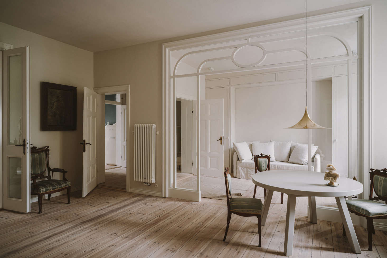 The view of the sitting and living rooms. The two-bedroom apartment was taken down to the studs; the only original features that were kept were the pine floors (sanded and oiled) and a fireplace. For the walls, Chrapka chose a soft white achieved by mixing Farrow & Ball&#8