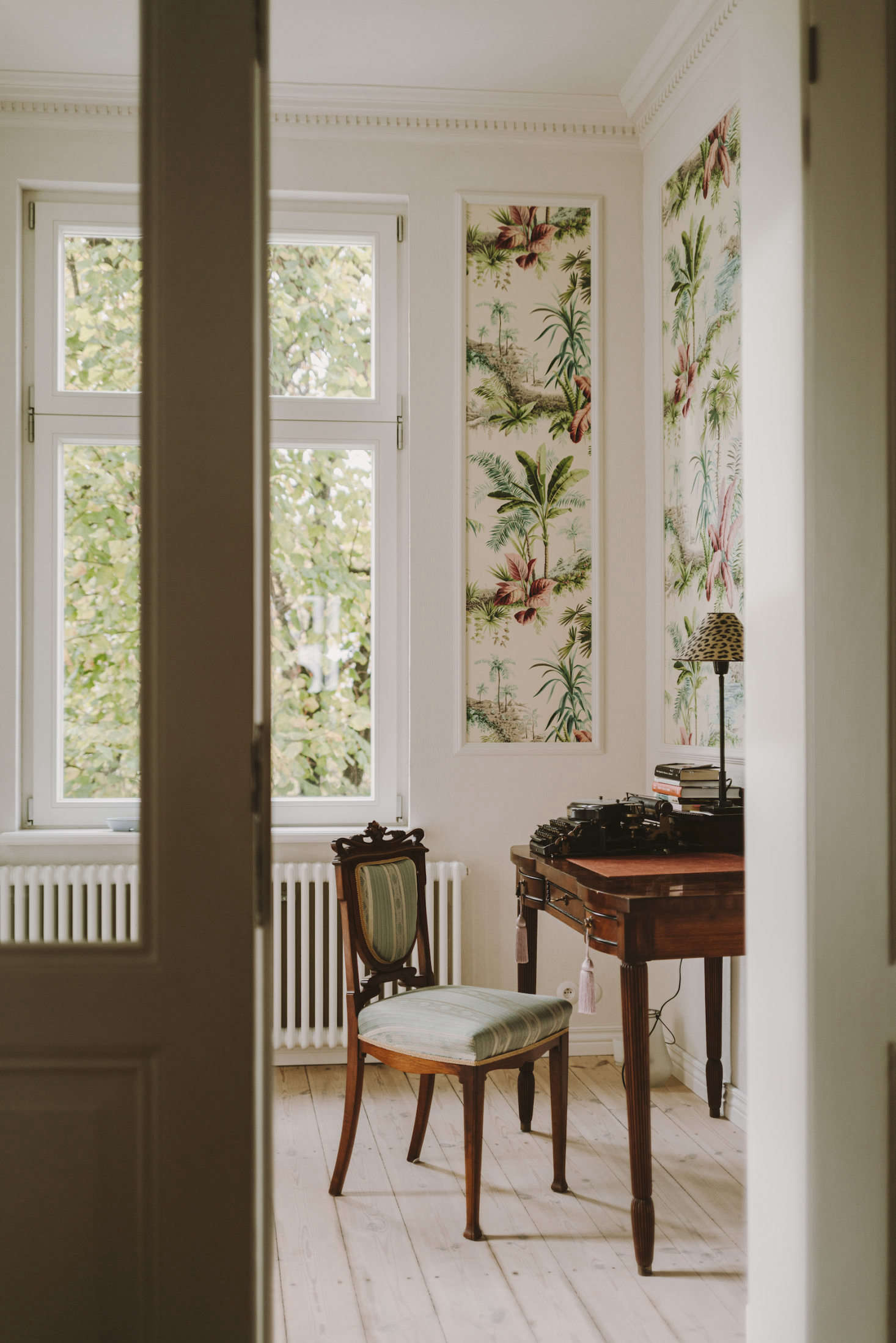 In a departure from the pale walls elsewhere in the home, the office features tropical &#8