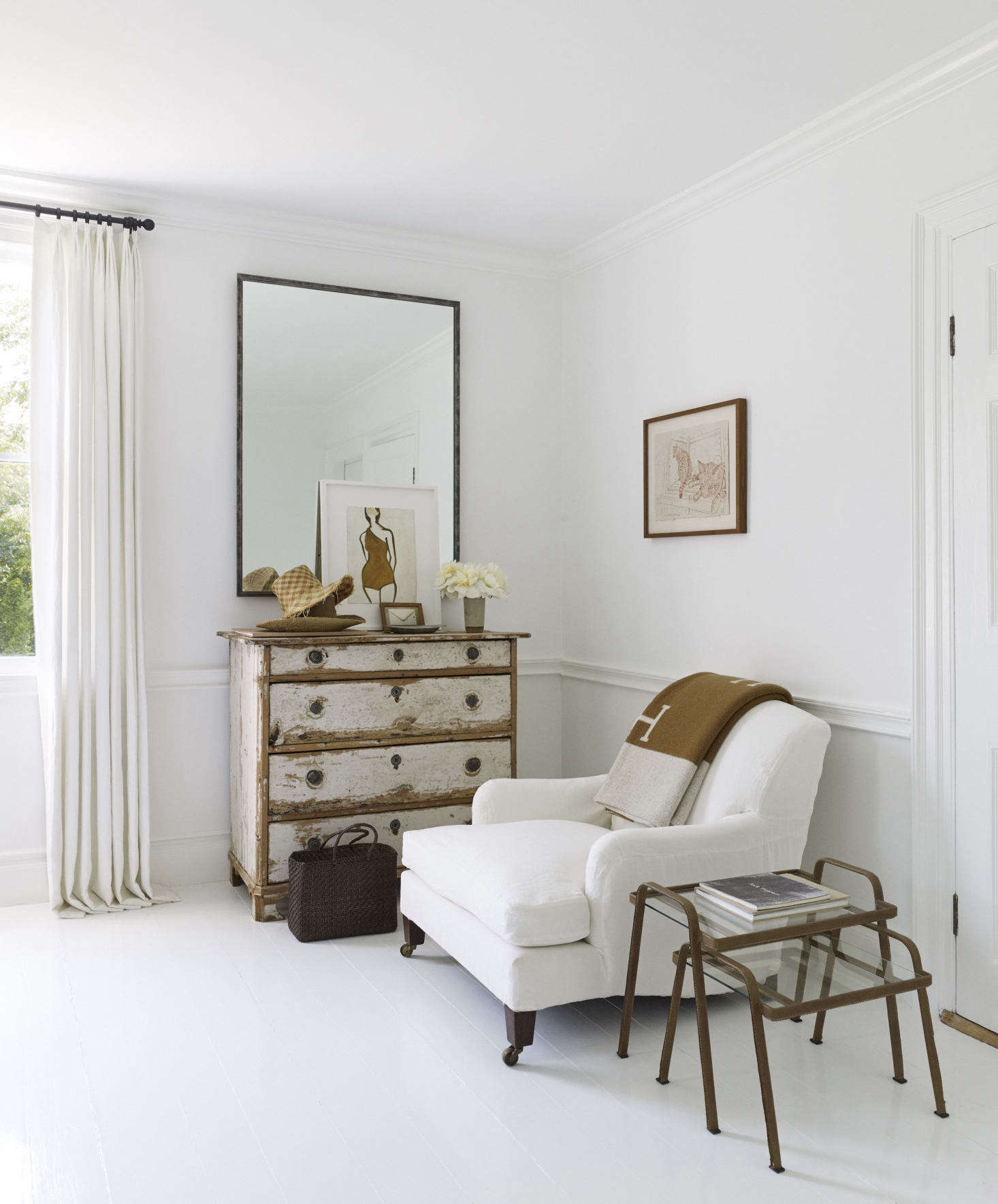 An antique chest from Bloom and an armchair from Ralph Lauren Home. The floor is painted in a high-gloss white enamel from Benjamin Moore.