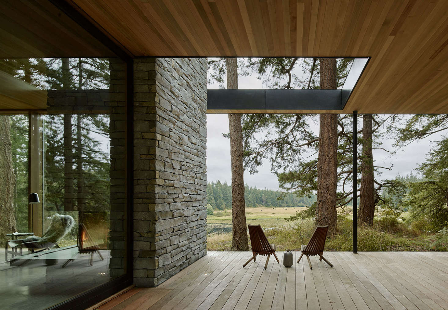 On the deck, the fireplace transitions into a stone wall. A cutout in the roof allows for more light.