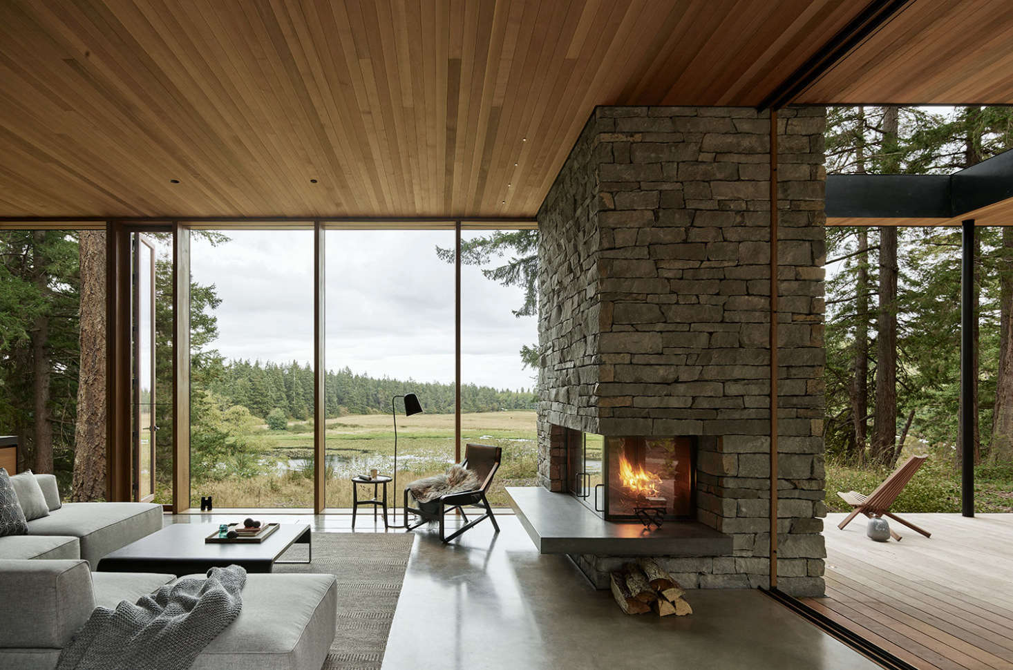 A portion of the stone fireplace rests on the deck just off the living room, blurring the line between indoors and out.