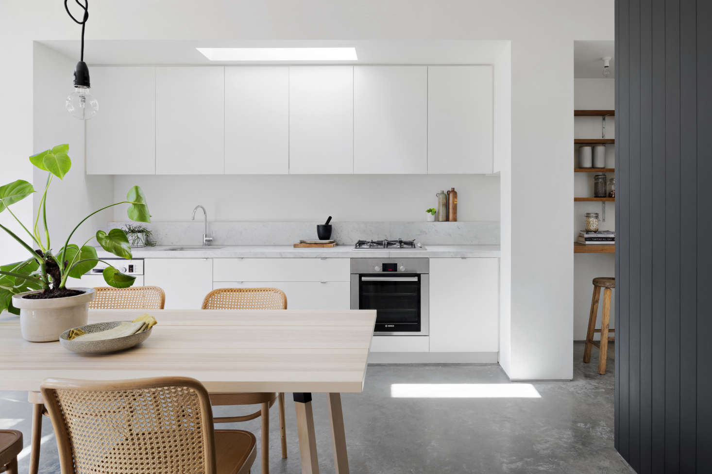 Kilpatrick carefully stuck to a palette of whites and grays offset by warm wood tones. A frameless skylight over the kitchen further brightens the space.&#8