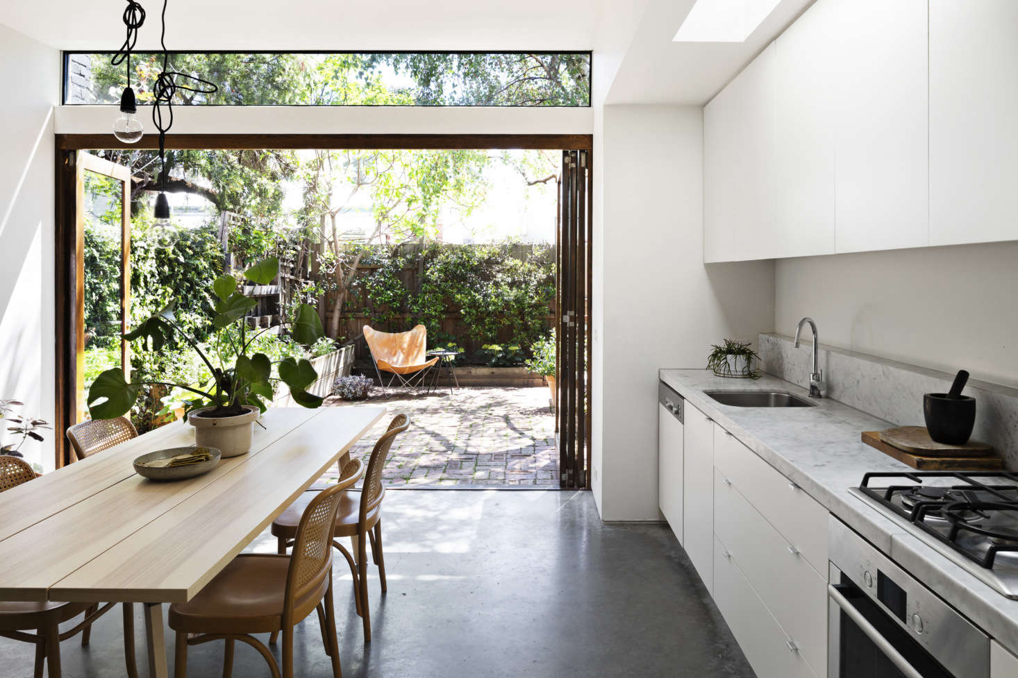 A polished concrete floor adds to the indoor-outdoor vibe. The kitchen cabinets are a flat-pack design that Kilpatrick and her husband painted and assembled themselves—&#8