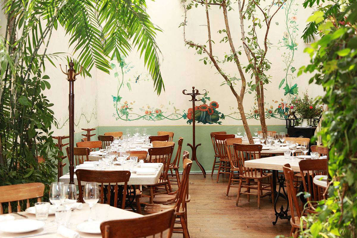 The greenery filled dining rooms have floral frescos, classic Thonet coat racks, and tables dressed in simple white linens.
