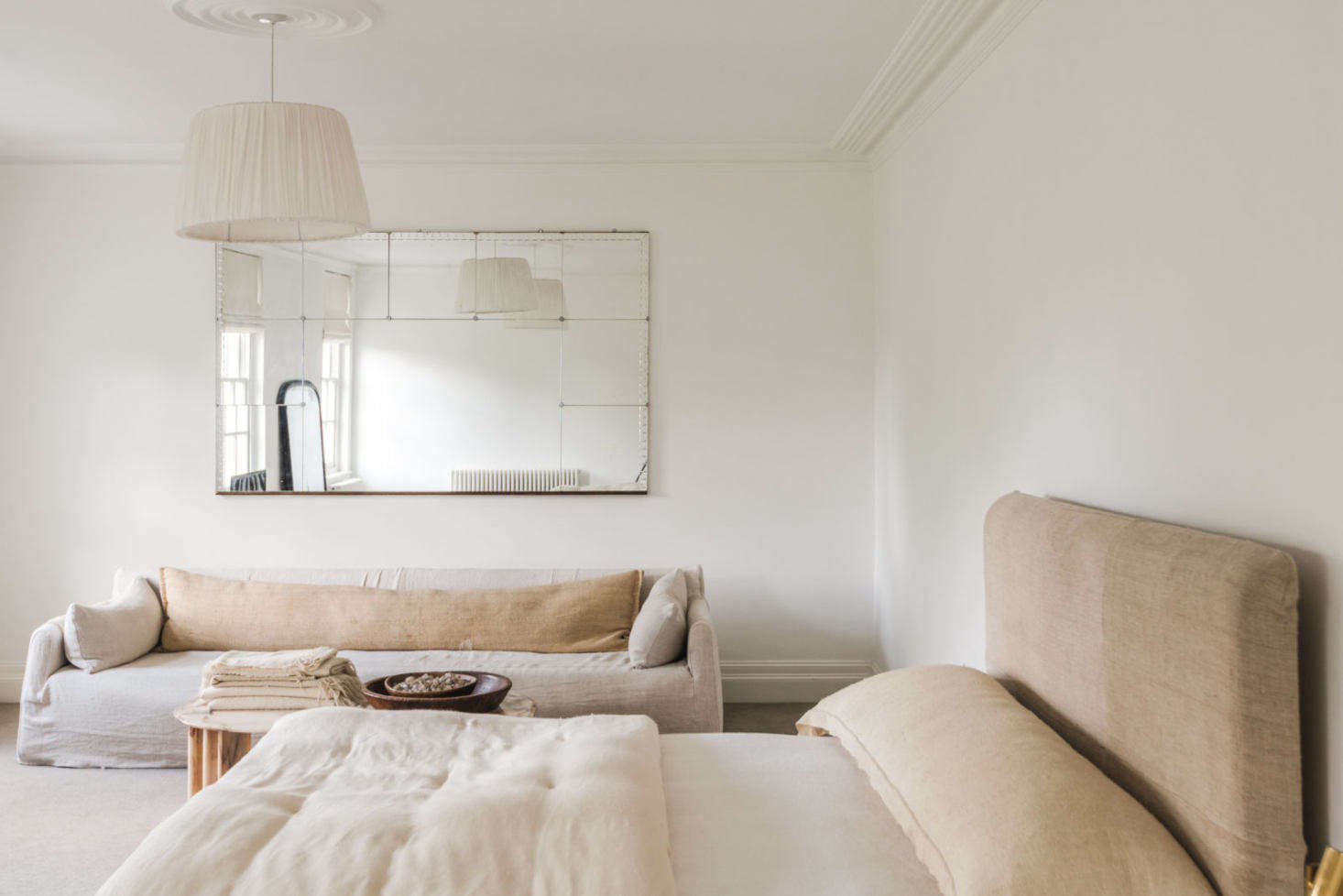 A linen-upholstered bed and sofa—both from Caravane—in a guest room.