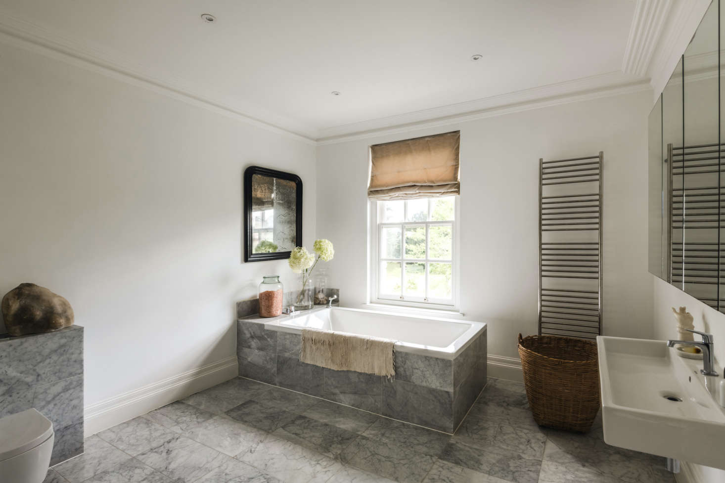 The master bath is tiled in gray-veined marble that rises to enclose the tub. The trough sink and towel rail are from C.P. Hart.