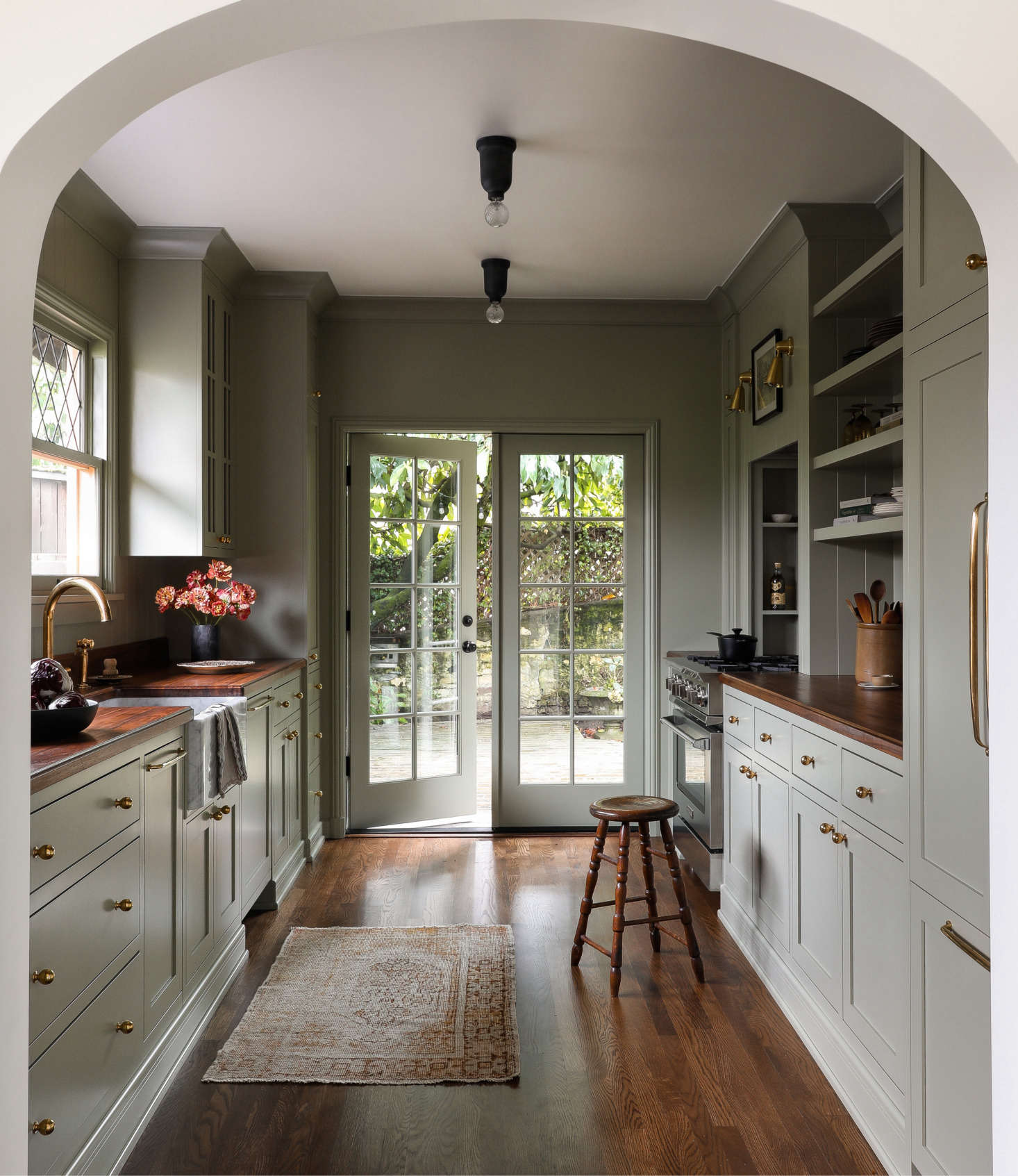 The custom galley kitchen references designs by leading UK design firms deVol and Plain English. The cabinets and walls are painted the same color—Farrow & Ball&#8