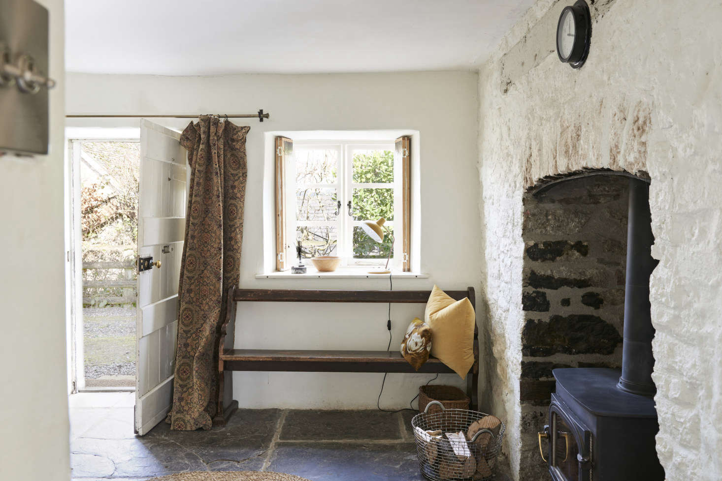 The front door leads to a rustic entrance hall with its original flagstone floor intact. Justine installed a curtain in front of the door for reasons both aesthetic and practical (it helps with the drafts).