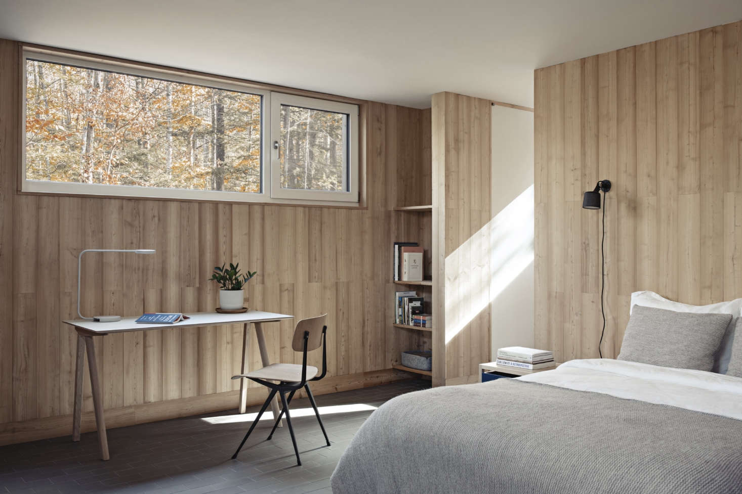 Paneled in larch, the bedrooms have a modernist cabin feel. The desk is the Copenhague 90 by Hay and the bedside sconces are Wall Spots by Vipp.