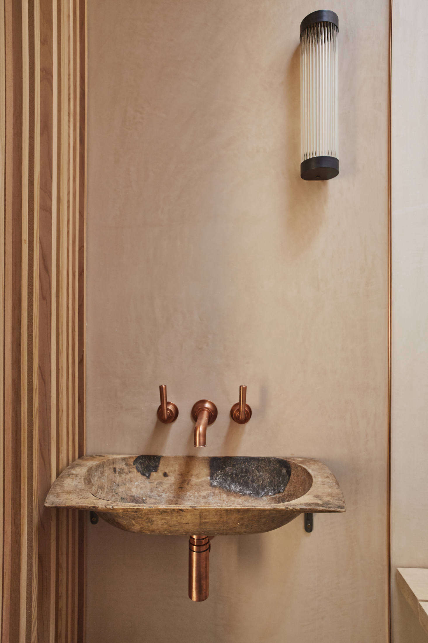 The basin is made from an old wood bread trough. The copper fixtures are from Waterworks.
