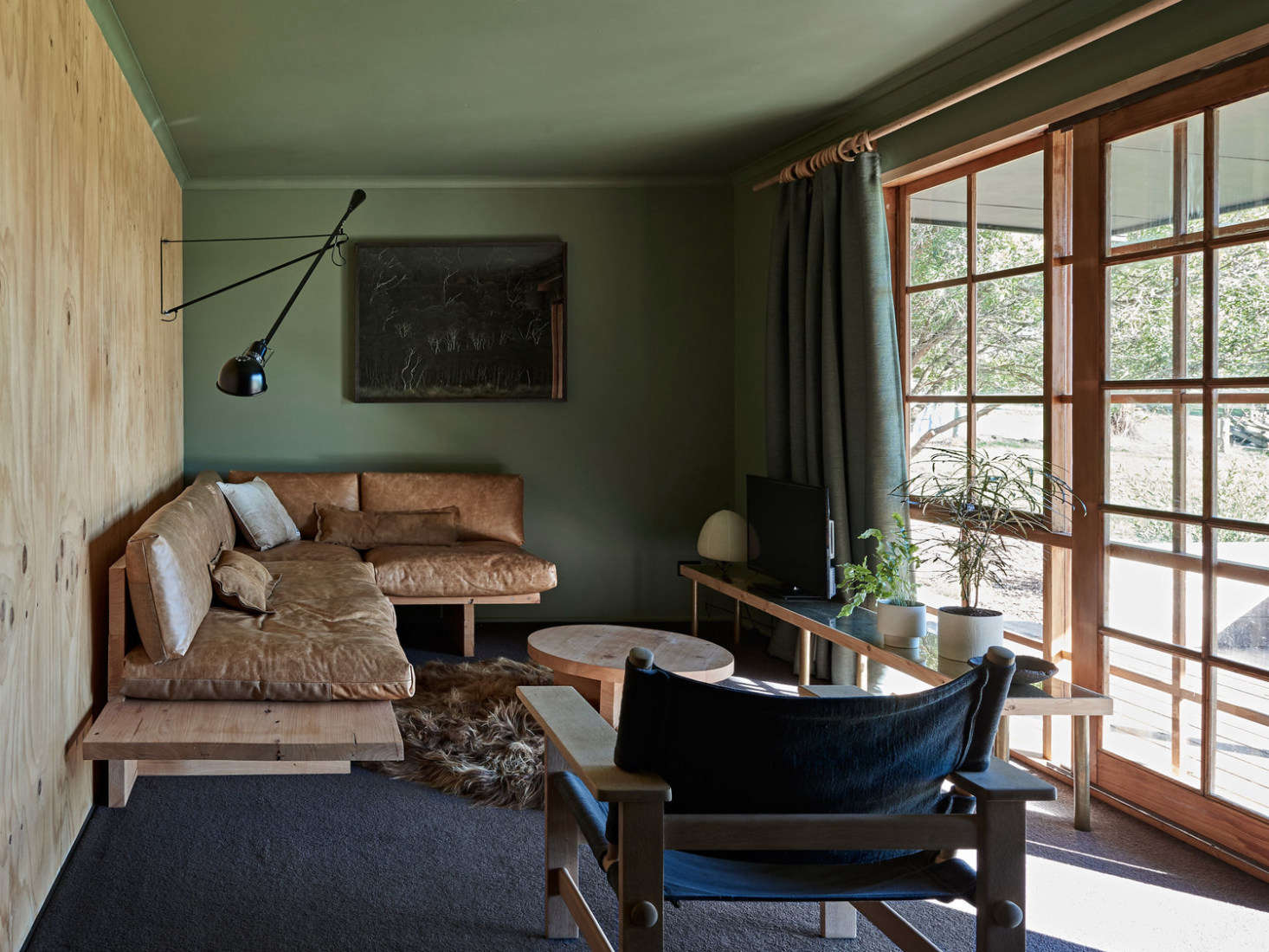 Plywood meets sage and worn leather in the living room. The cedar-framed French doors were introduced to make the most of the views. (&#8