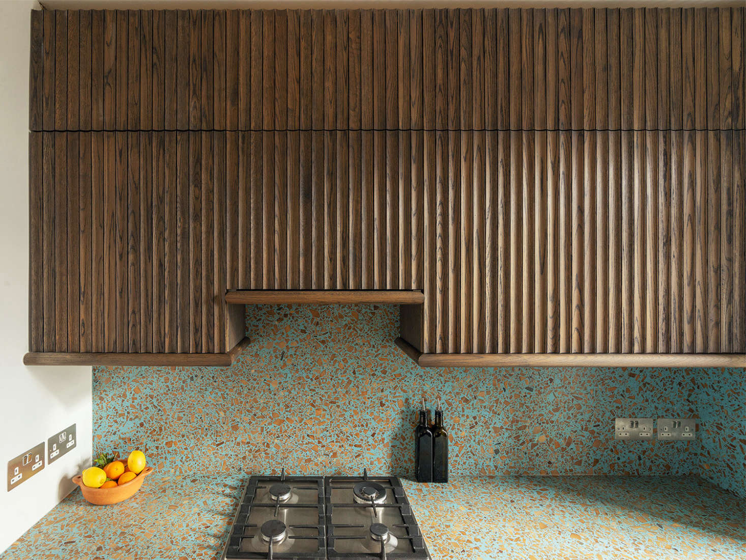 Fluted oak cabinets meet terrazzo in a compact London kitchen by Surman Weston architects. The counter and backsplash are Foresso, a composite sheet material made from, among other things, scrap wood, waste from sawmills, and waste lime plaster.