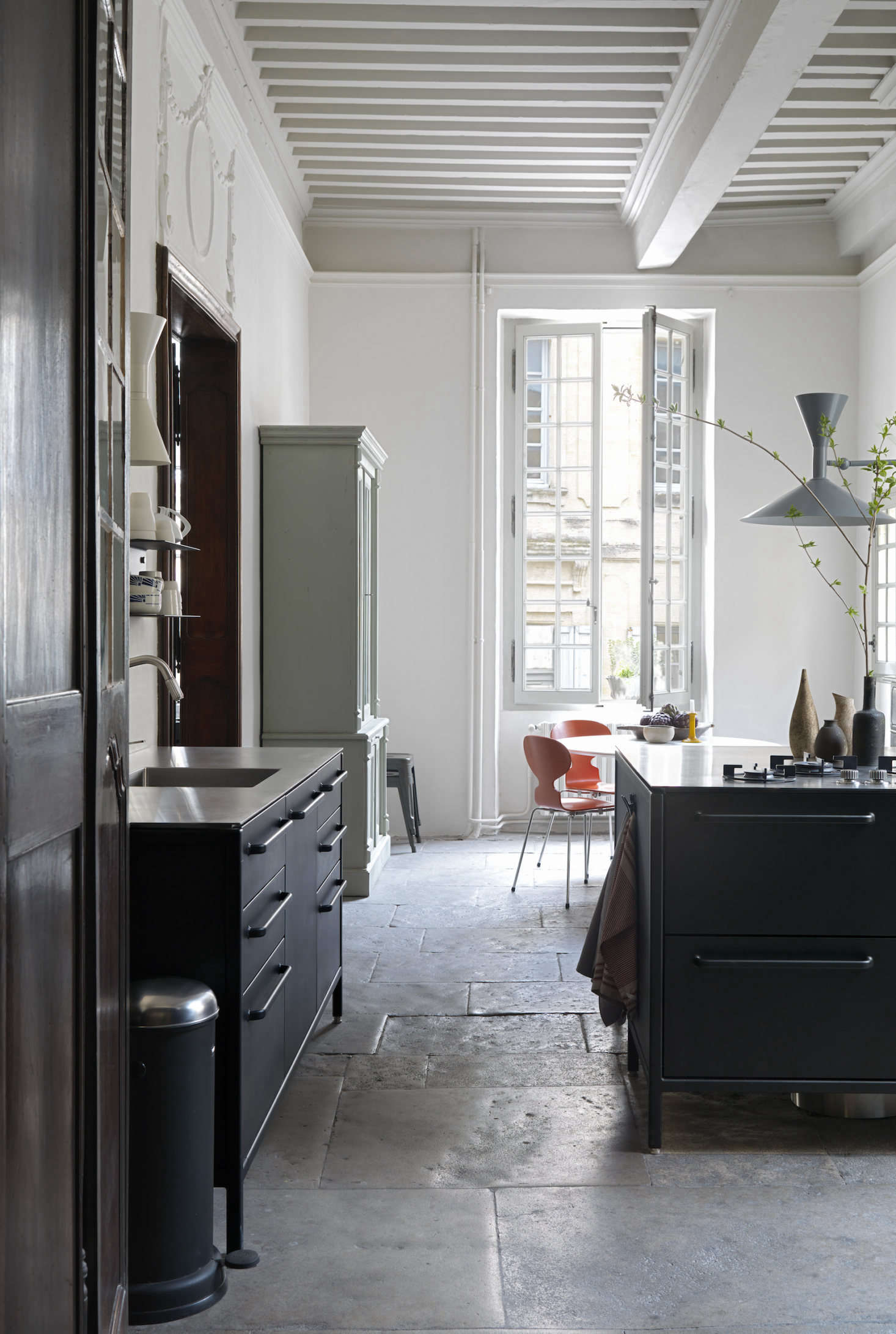 A vintage painted hutch offers a warm contrast in the kitchen. Note the -foot-high ceiling.