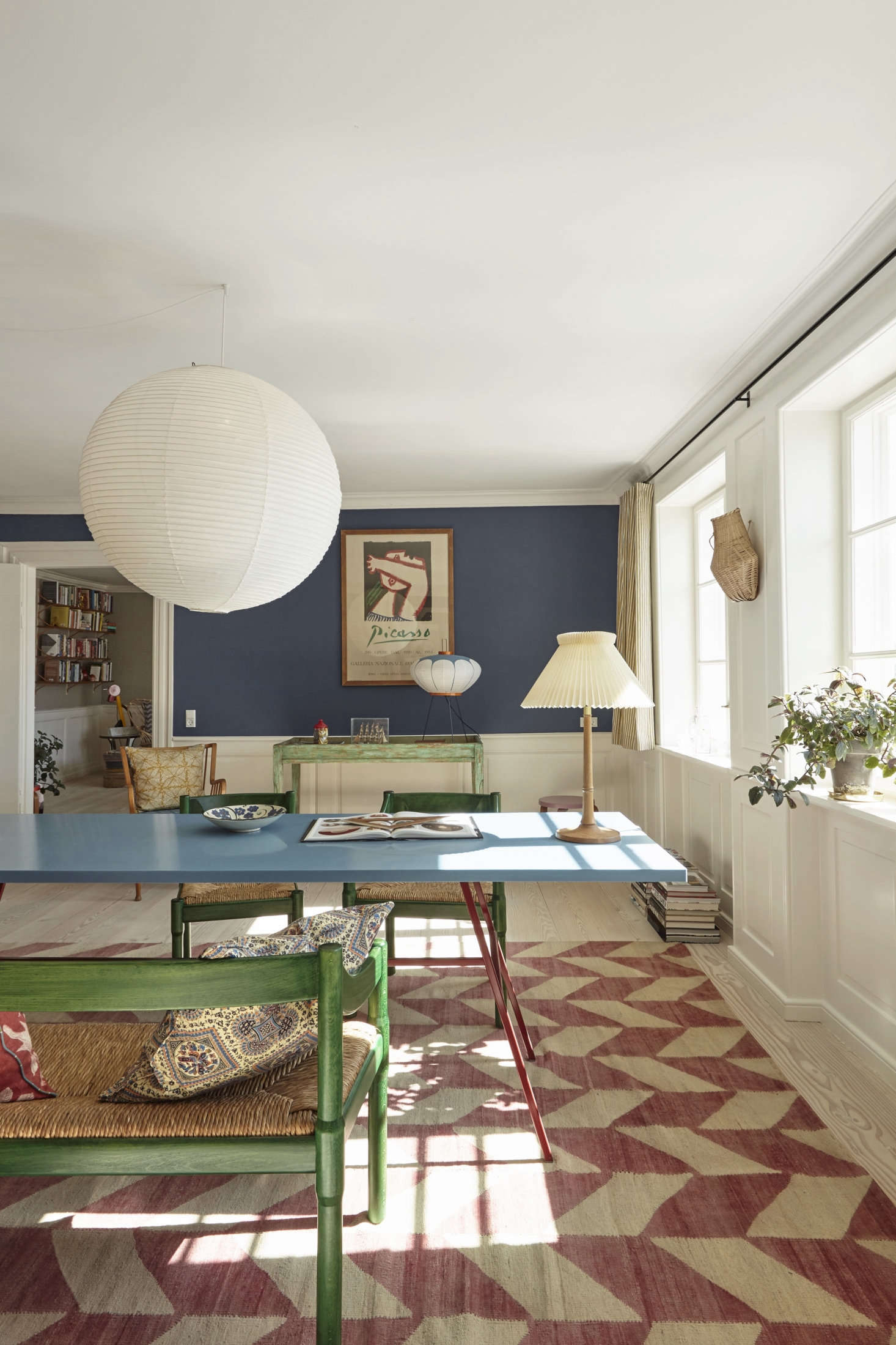 The walls are painted Farrow & Ball Drawing Room Blue. The dining chairs are a Vico Magistretti design from 59.