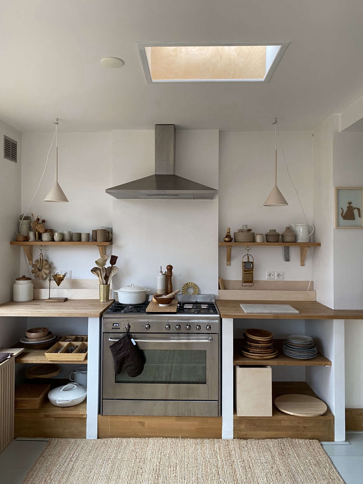 Open shelving in the kitchen (even their flatware is on a shelf and not in a drawer) means they have to be mindful of keeping clutter at bay. A sisal rug in the kitchen makes for an extra-cozy vibe.