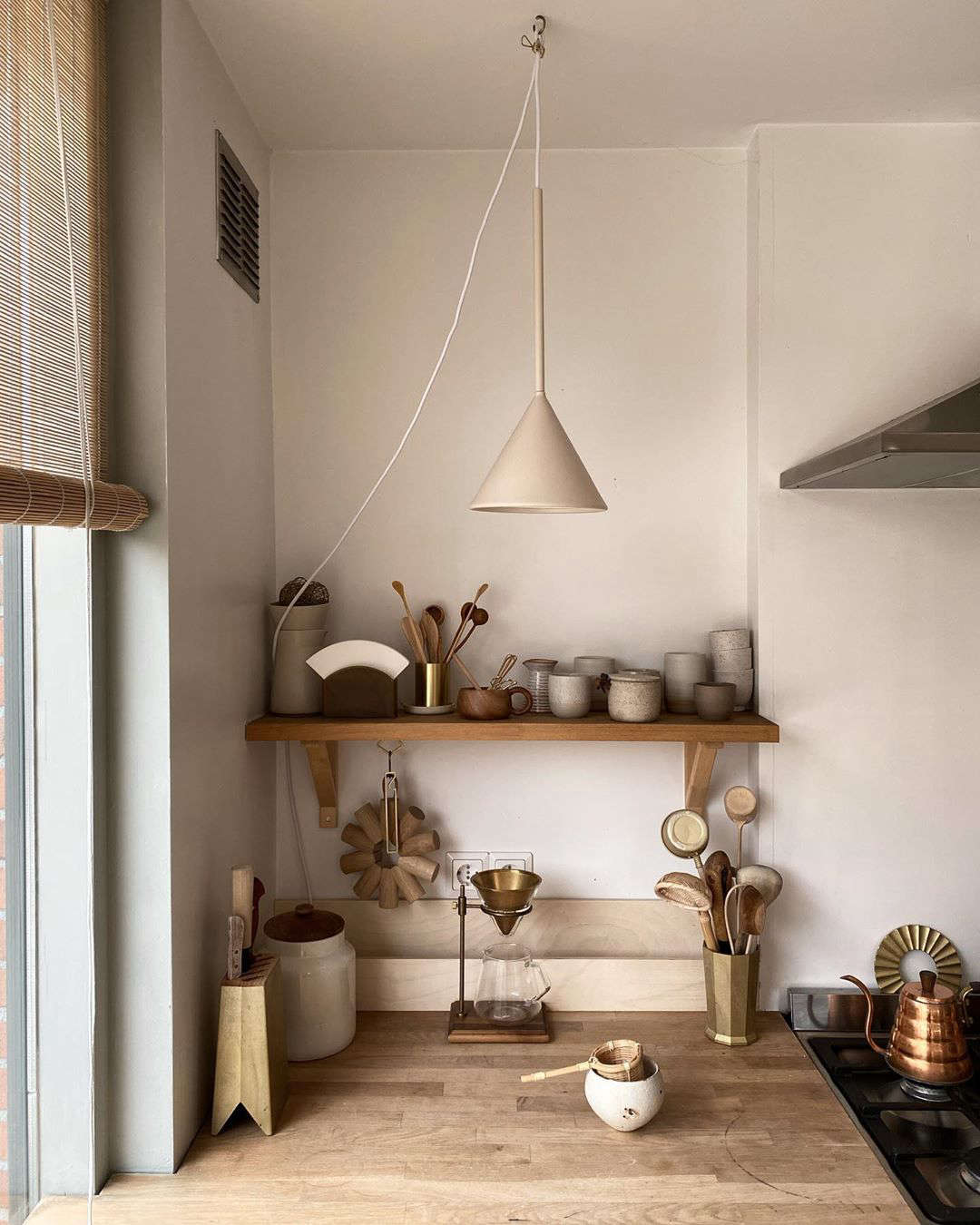 Confirmation of their admiration for Japanese design: an impressive collection of brass Futagami objects. The couple also collect Japanese ceramics. The cone pendant lights are by Schneid Studio.