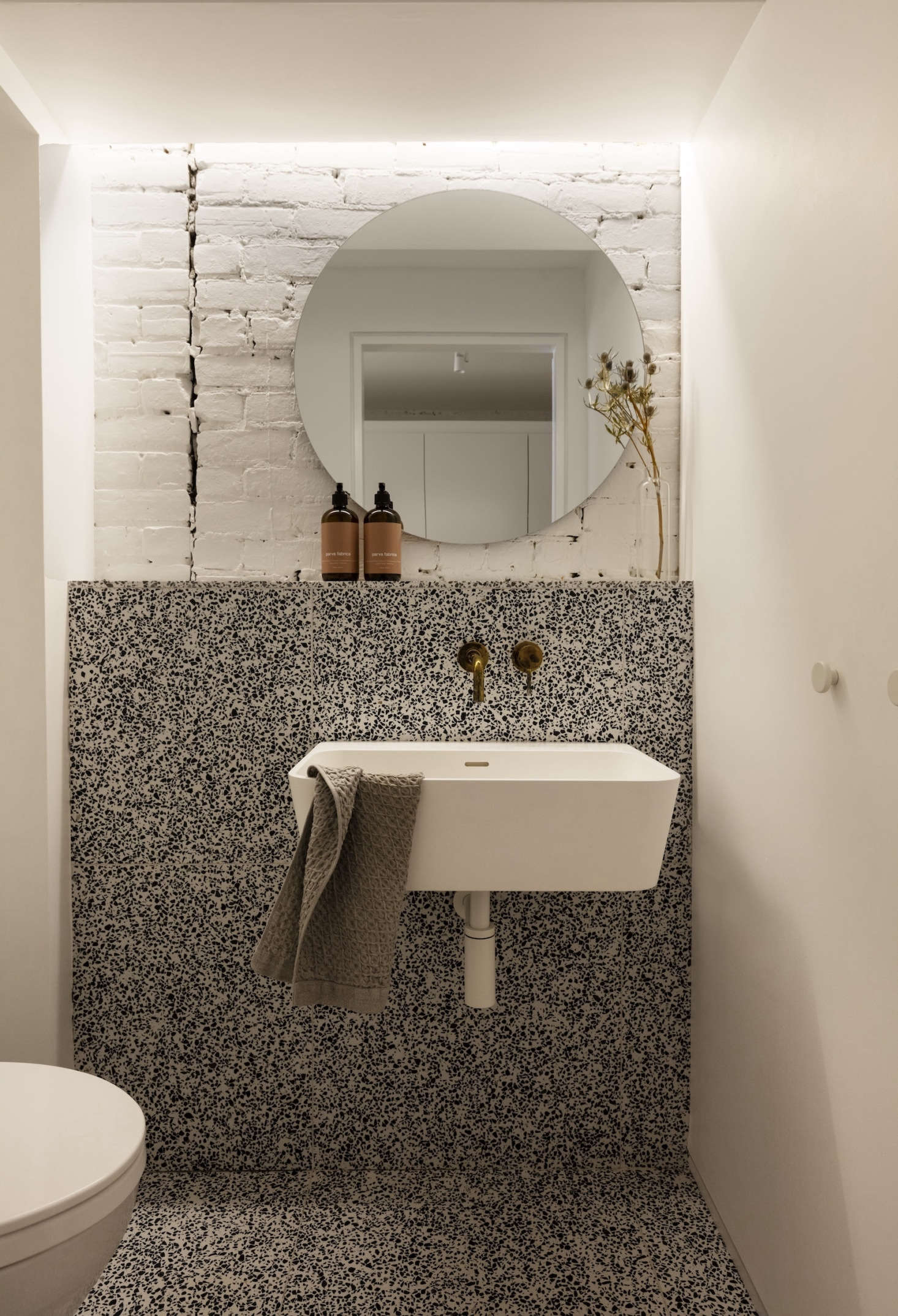 The terrazzo powder room, featuring a sink from Porcelanosa.