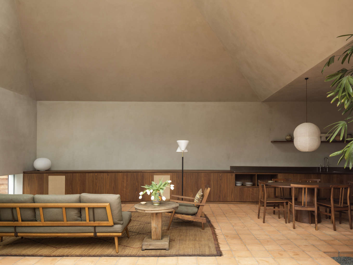 A wider view of the living room and open kitchen. Without a kitchen island, the architects note, the dining table becomes a central gathering space, connecting the two rooms as one.
