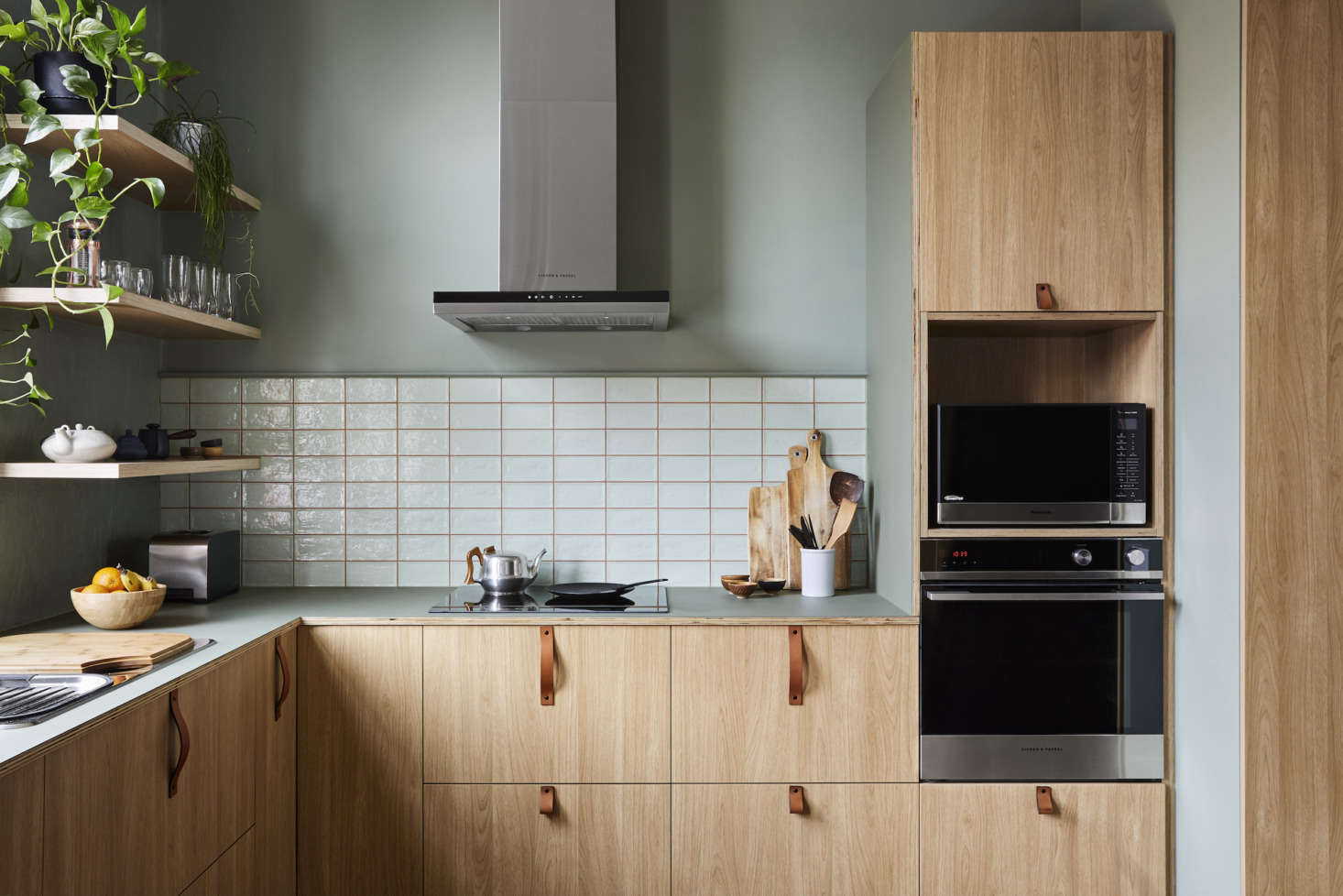 The kitchen references the outdoors with sage-green accents. On the walls here is Dollar by Australian paint company Dulux. The tiles are from the Piemonte collection (in apple) by Classic Ceramics.