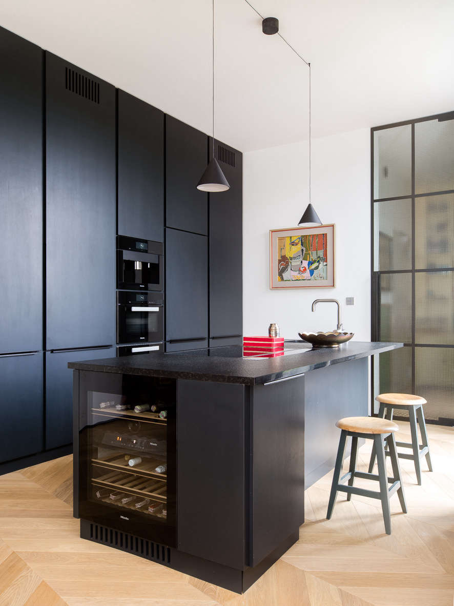 The kitchen has a sleek and sophisticated look thanks to stained ash cabinets, a black granite countertop, and integrated appliances. The String Cone Pendant Lights are by Michael Anastassiades, from Flos.