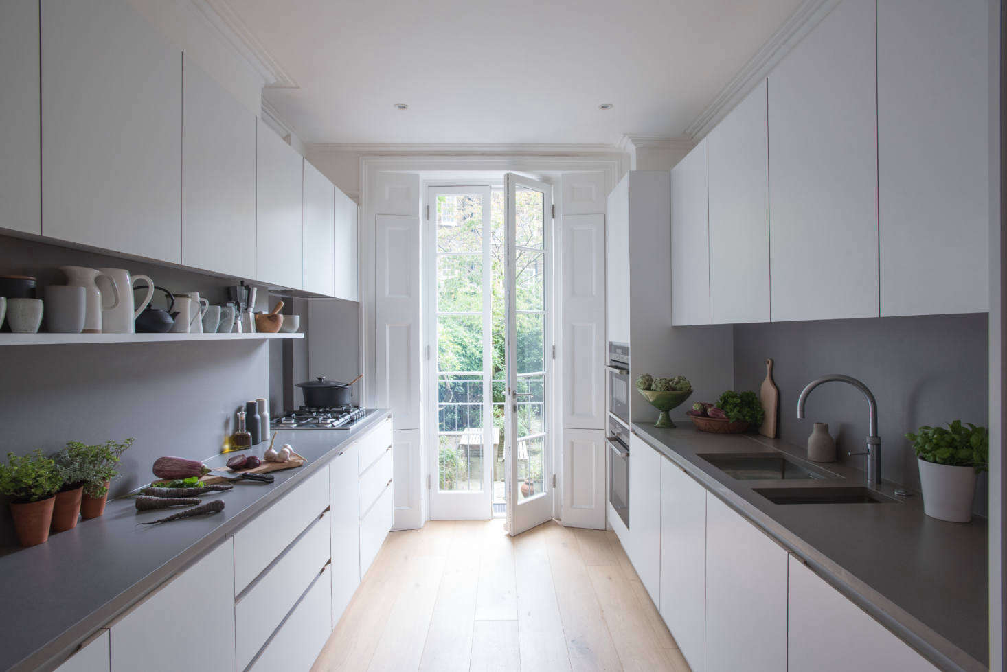 Composed of streamlined cabinets of laminate-clad MDF with oak edging, the kitchen has windows at either end: the French doors open to an eating area and garden. The design is known as the JT Original.
