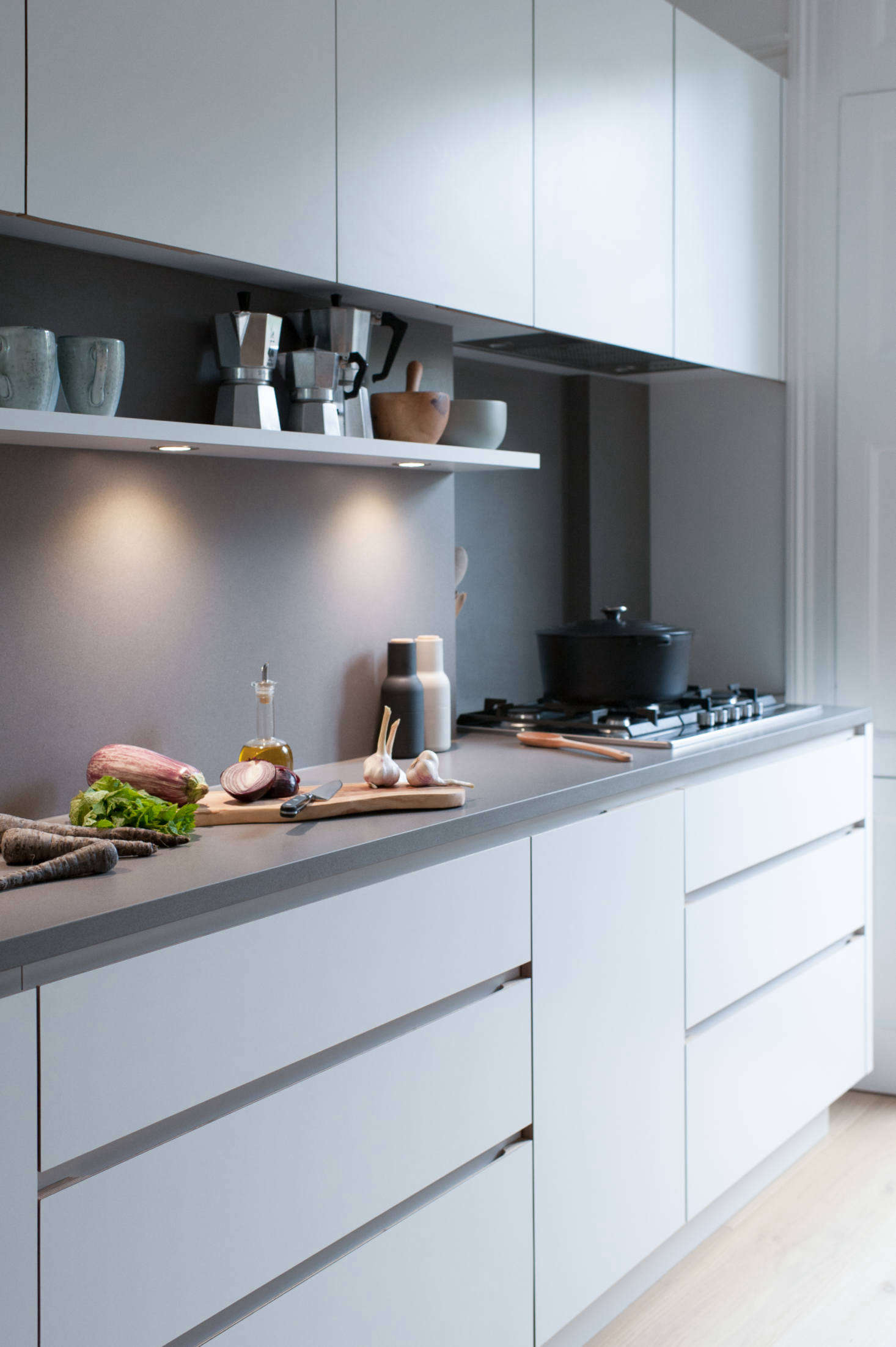 The counters are Silestone in Gris Expo, as are the backsplashes (with a suede finish). The five-burner cooktop is by Siemens and the under-cabinet extractor is the Weston Cache 700. Note the integrated under-shelf lighting. For tips on recessed lighting, read Expert Advice from Architect Oliver Freundlich.