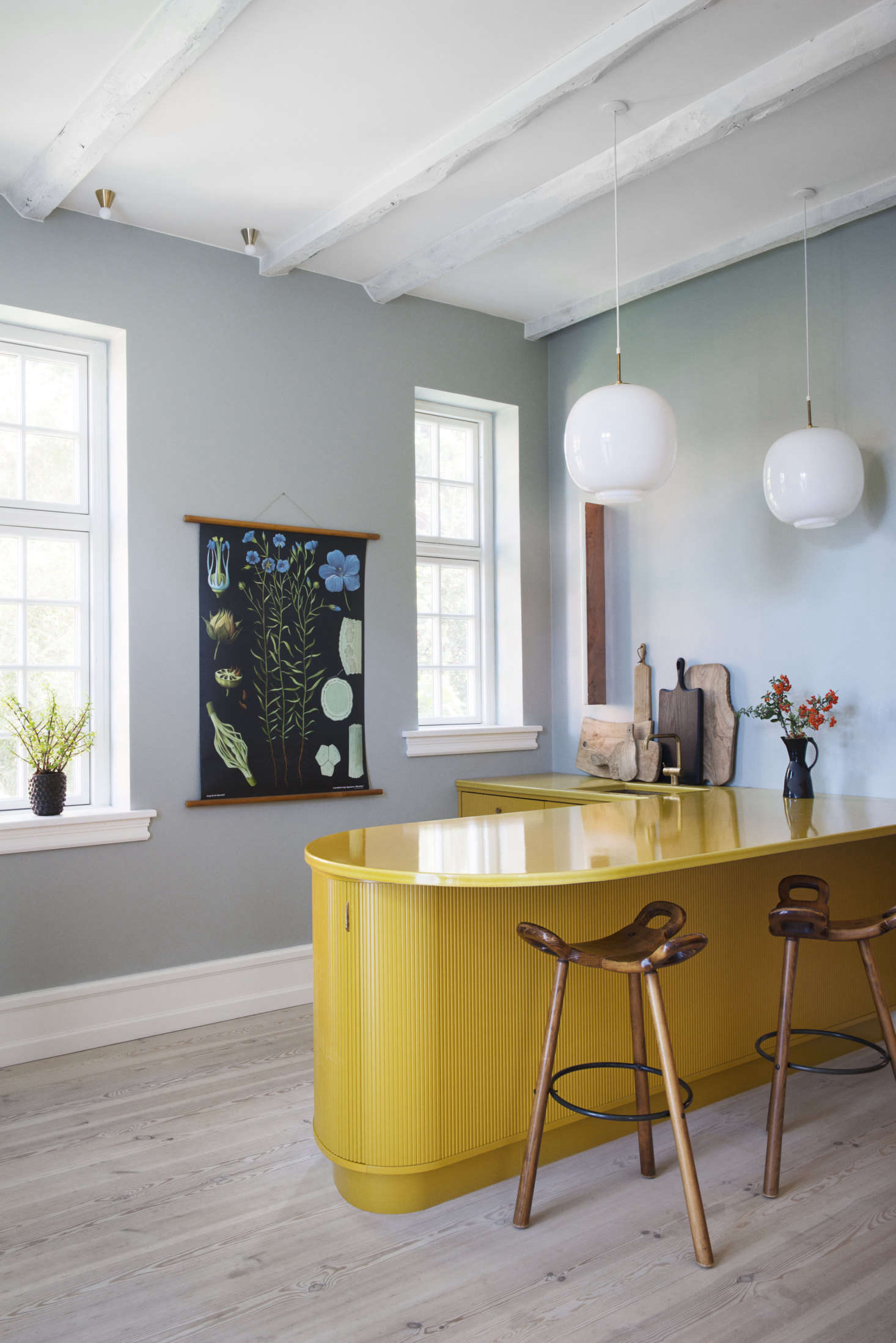 Master cabinetmakers KBH of Copenhagen outfitted this kitchen in Frederiksberg, Denmark, with a shiny sink and breakfast counter the color of curry. The cabinets are oak; the counter is glazed lava stone. Photograph by Gyrithe Lemche.