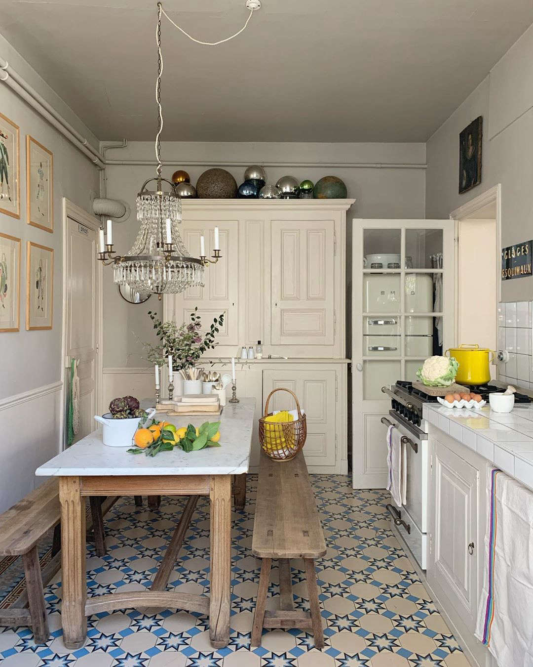 The petite kitchen, with glimpses of color (in a cloth, a yellow pot, a hanging market bag).