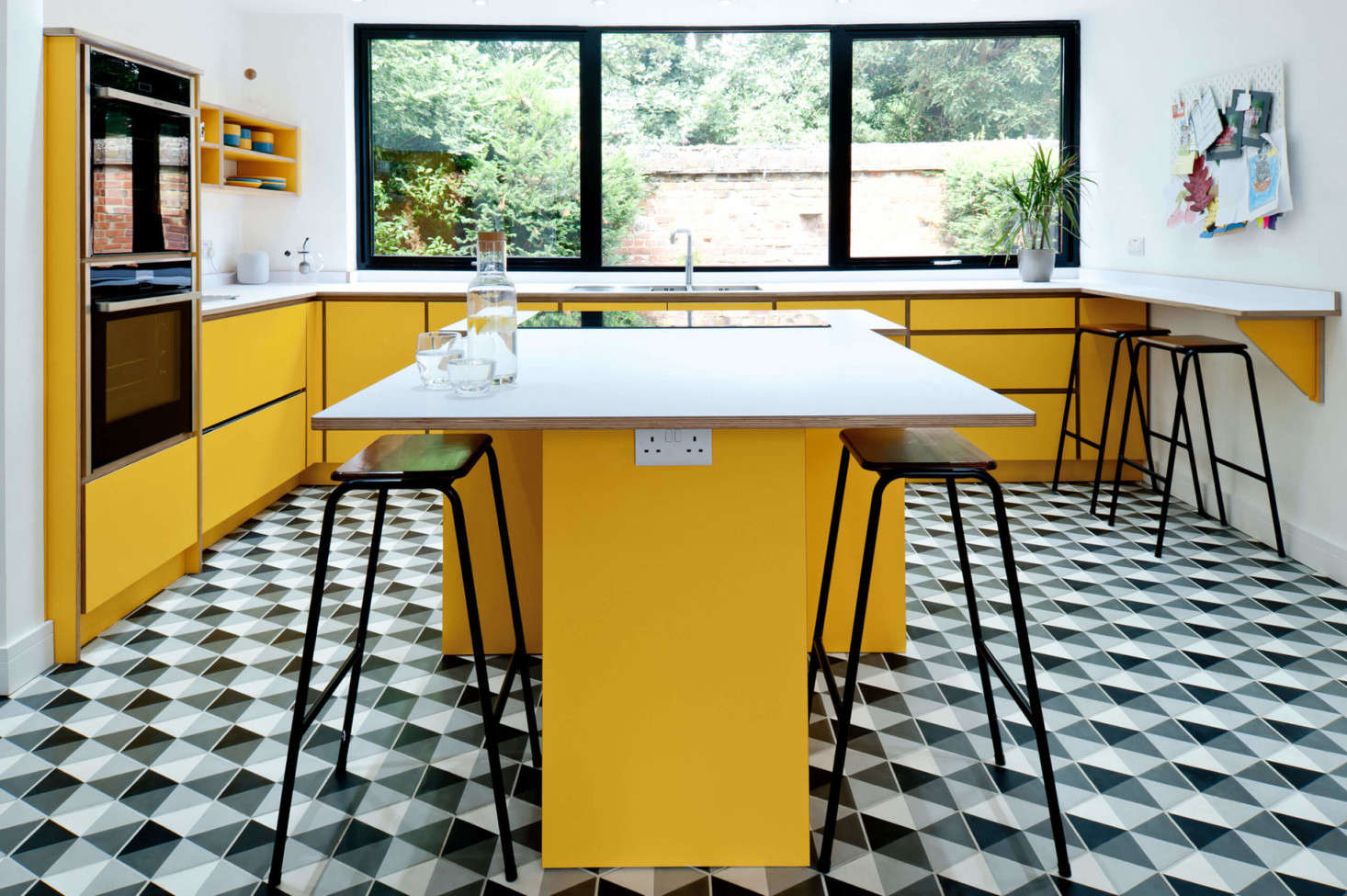 Bright Formica and birch plywood meet geometric tile in a South London design by Koivu, a husband-and-wife-run kitchen company based in Kent, England.