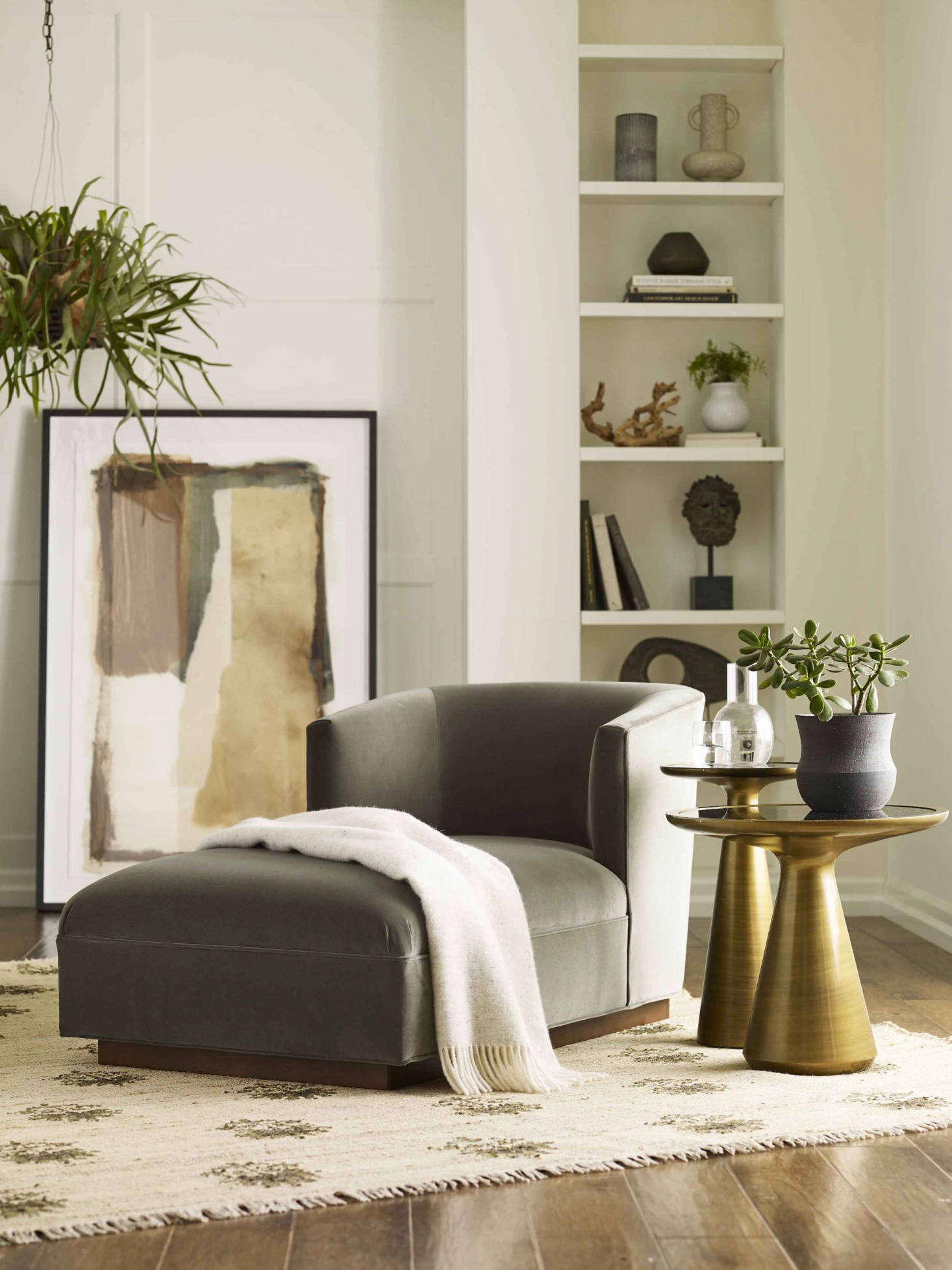 """Add a Cooper Chaise to a corner of the bedroom or living area and you have a ready-made retreat for a bit of calm and quiet. This one is shown in """"fern""""-hued velvet, paired with the sculptural Addie Side Table and Addie Pull-up Table in bronze and the hand-knotted Disha Rug (one of four new rugs made in collaboration with sustainable rug maker Obeetee)."""