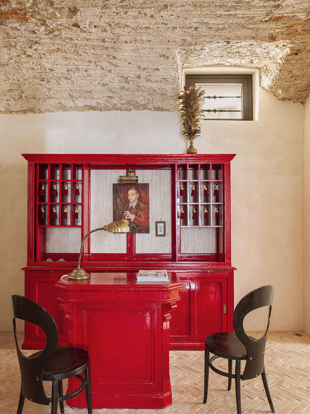Just add red lacquer: the front desk was created from two vintages pieces renewed with glossy paint. The surfaces here range from newly laid herringbone brick to freshly plastered walls and a ceiling preserved in its excavated state.