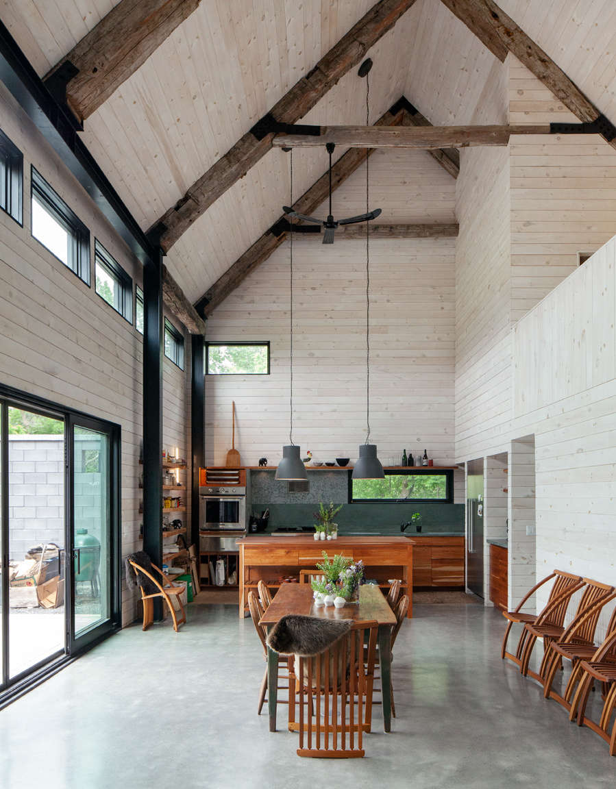 The open space in the addition features polished concrete floors, white-washed pine walls, and salvaged timber ceiling beams. The slatted dining chairs by Canadian designer Thomas Lamb were a gift from Victoria&#8