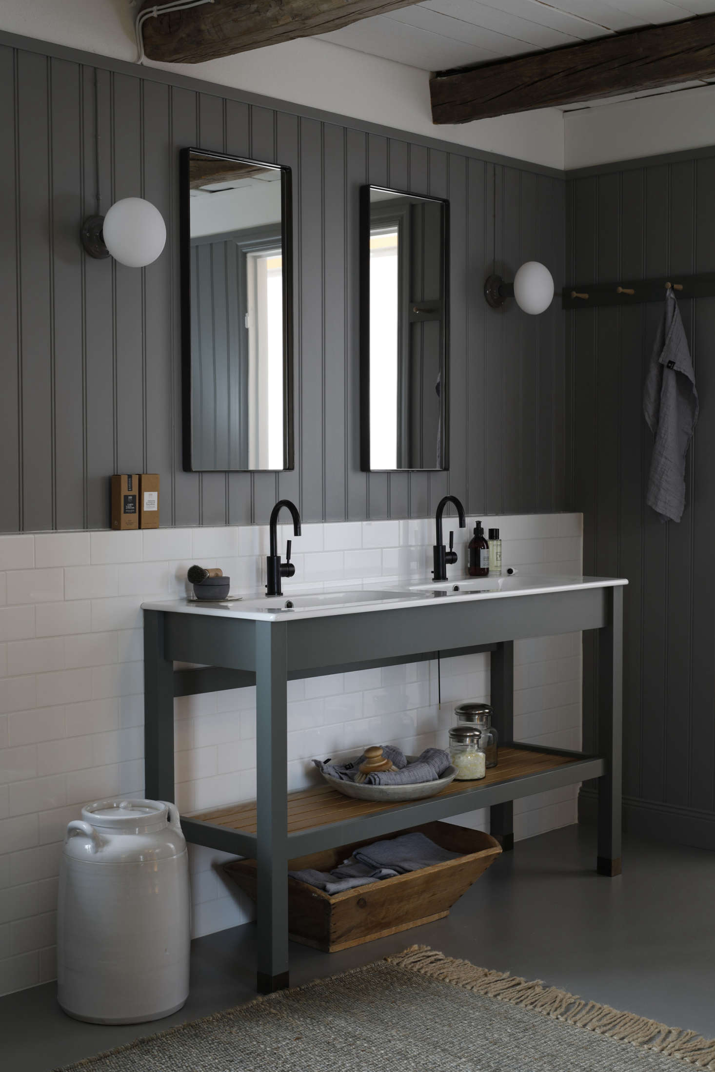 Italian sinks with Dornbracht Tara faucets are set in a Kvänum vanity with a slatted storage shelf. Note the subway-tiled backsplash against beadboard-paneling in a warm gray from Norwegian paint company Jotun (NCS code 650