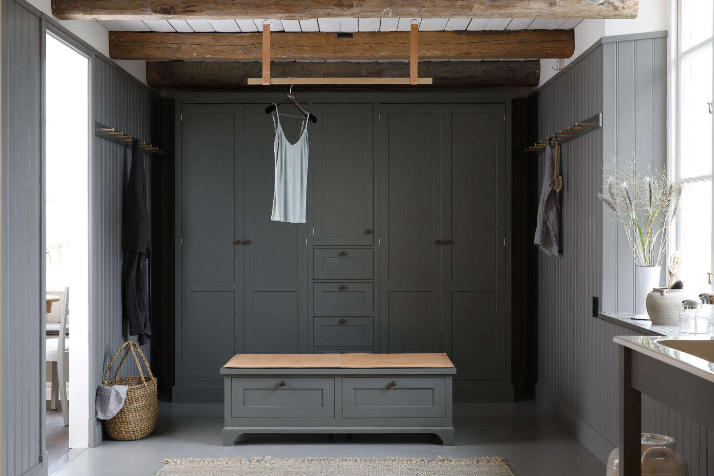 A leather-cushioned bench overlooks a bank of built-in closets and drawers for two. The leather-and-wood hanging bar is another Kvänum detail: the company, which dates to , specializes in custom kitchens and closets created from elements in its catalogue: this is the Modern Classic Dressing Room in Ekeby Forest Green, an in-house paint color.