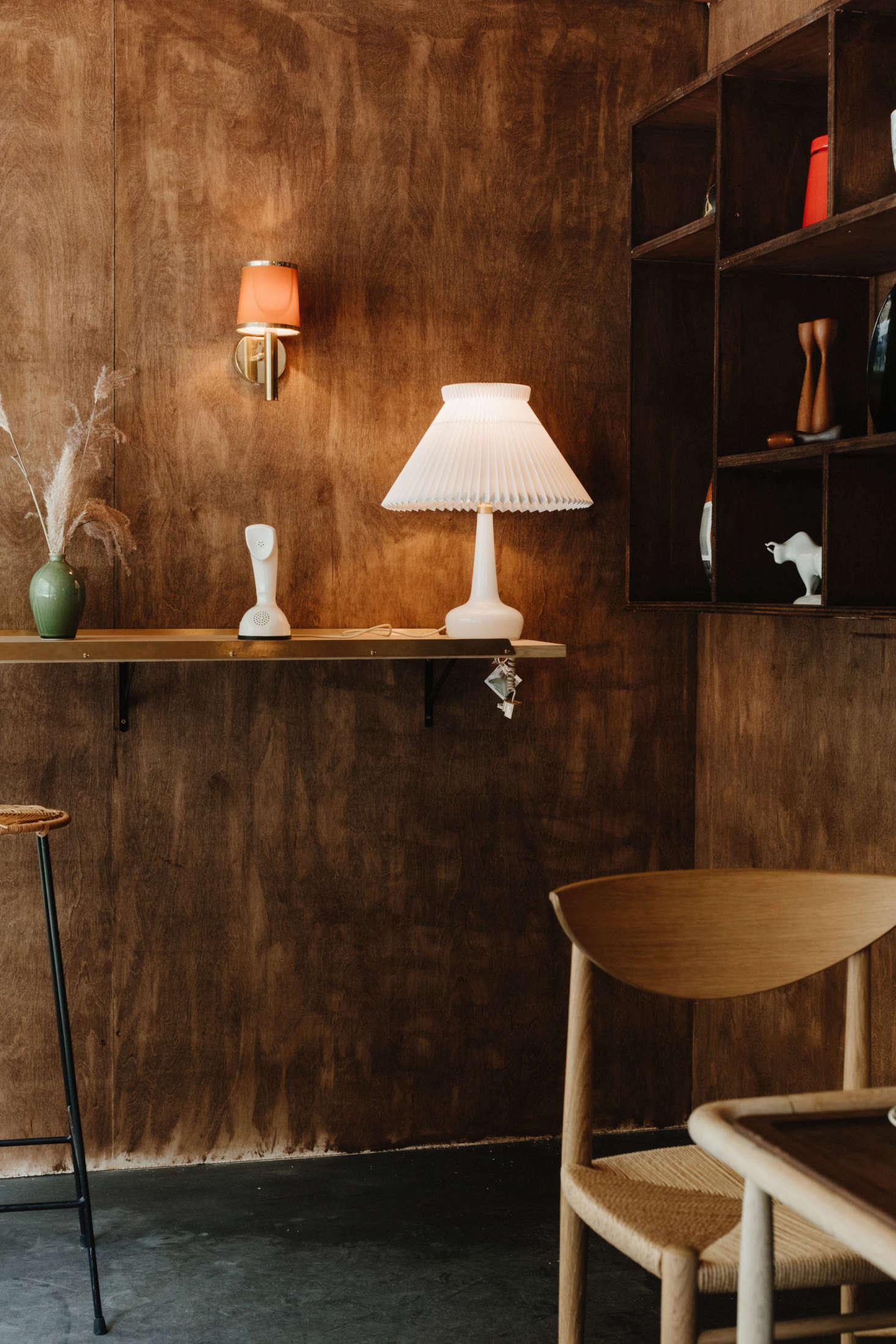 Na prateleira: um abajur Le Klint com base em vidro da Holmegaard.  Também é retratado um Cobra Phone vintage da Suécia e um vaso de cerâmica canadense de meados do século com vidros verdes.