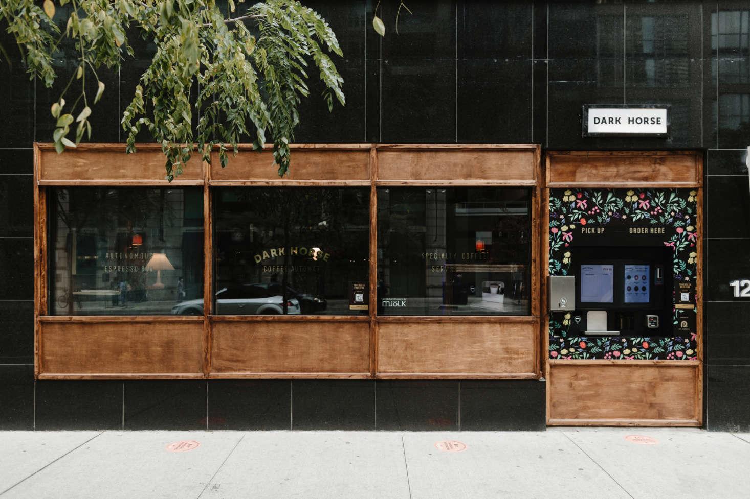 A fachada apresenta uma estação de pedidos ao ar livre;  os transeuntes podem espiar pela janela o interior de uma cafeteria em formato de palco.