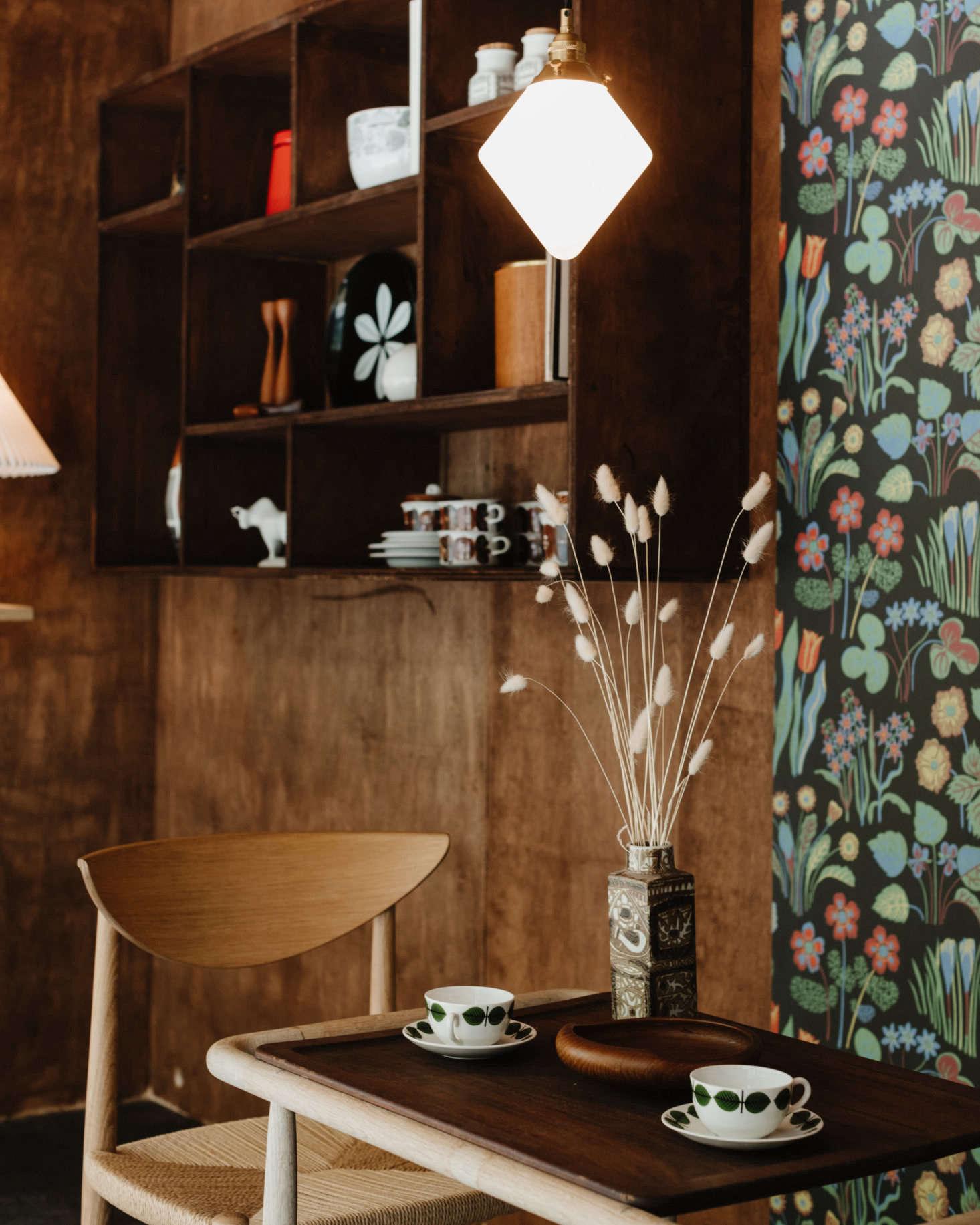 A mesa é posta com xícaras de café Bersa vintage de Stig Lindberg para Gustavsberg e uma tigela de teca dinamarquesa vintage.  O Nils Thorsson Stoneware Vase é do Royal Copenhagen, e a Diamond Pendant Light pendurada acima foi projetada por Oji Masanori para Mjolk.