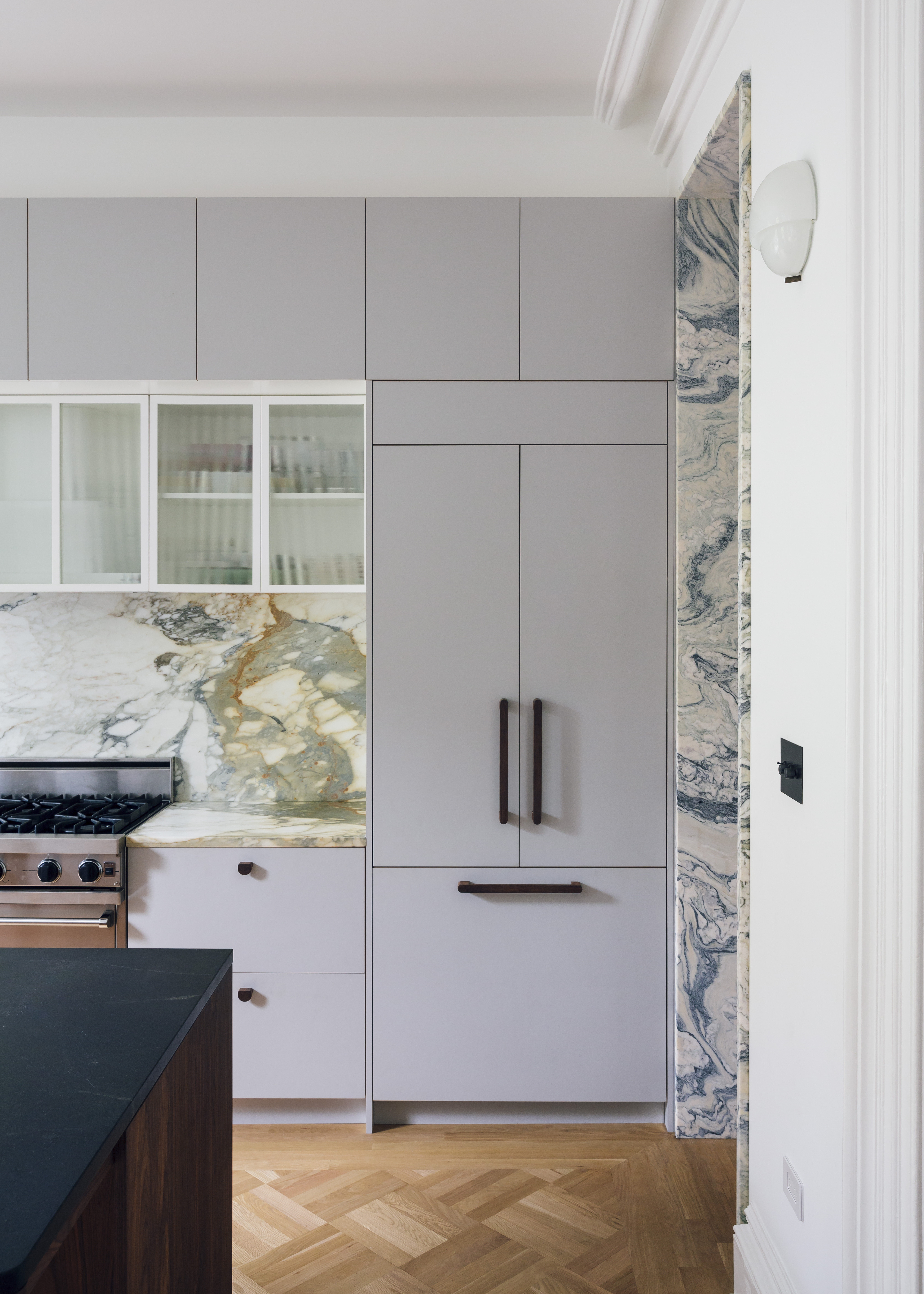 The kitchen is kept neat thanks to tucked-away appliances, like an integrated refrigerator hidden behind cabinet fronts and a vent hood tucked into the custom reeded-glass upper cabinets. The walnut pulls were custom-designed by Civilivn.