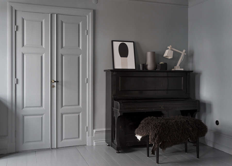 An upright piano with sheepskin-draped bench anchors a corner of the living space.
